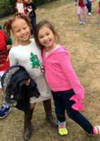 Two girls smiling during Jingle Bell Jog.